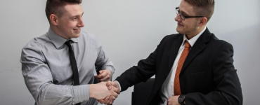 A hiring manager shaking hands with an interviewee, offering him the job.