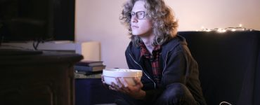 Man watching a horror movie with a bowl of popcorns for Halloween marathon