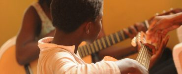African-America child in a guitar-learning class