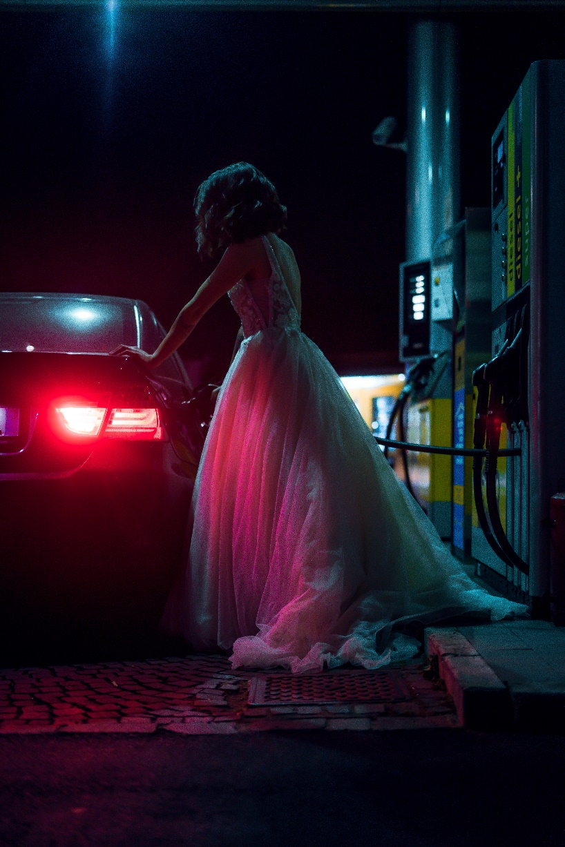 A woman in a white dress getting inside the car