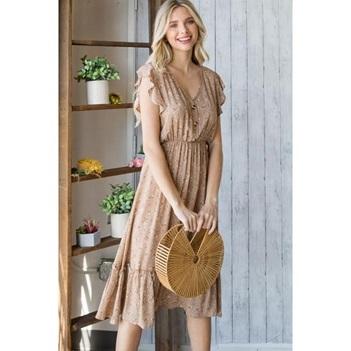 A woman wearing a beige summer dress.