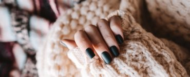 Woman in a sweater with black gel nails