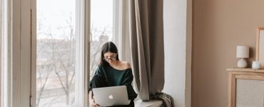 A Bespectacled Female Perched Upon a Window Seat with a Notebook and Coffee Mug