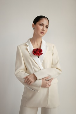 A woman posing in a while pantsuit.