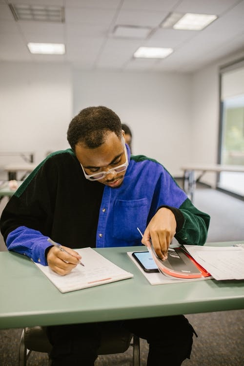 A student cheating during an exam as he uses Internet sources for plagiarism.